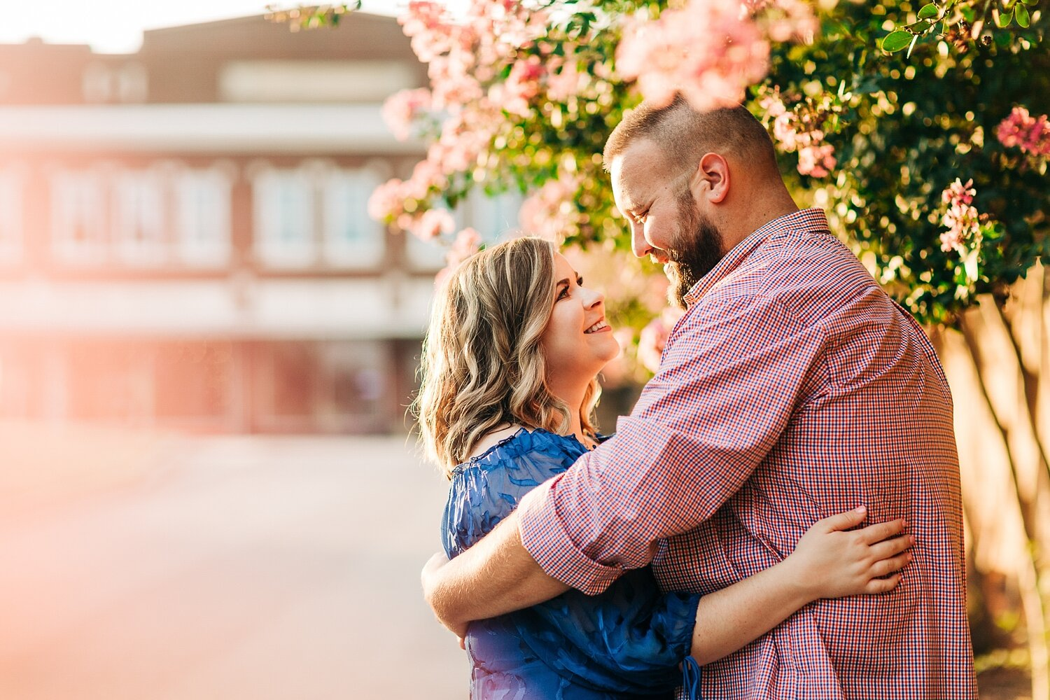 engaged couple embraces under a blooming crepe myrtle