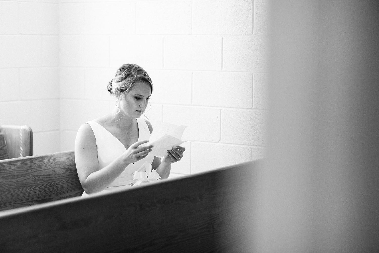 bride reads a letter sitting in a church pew