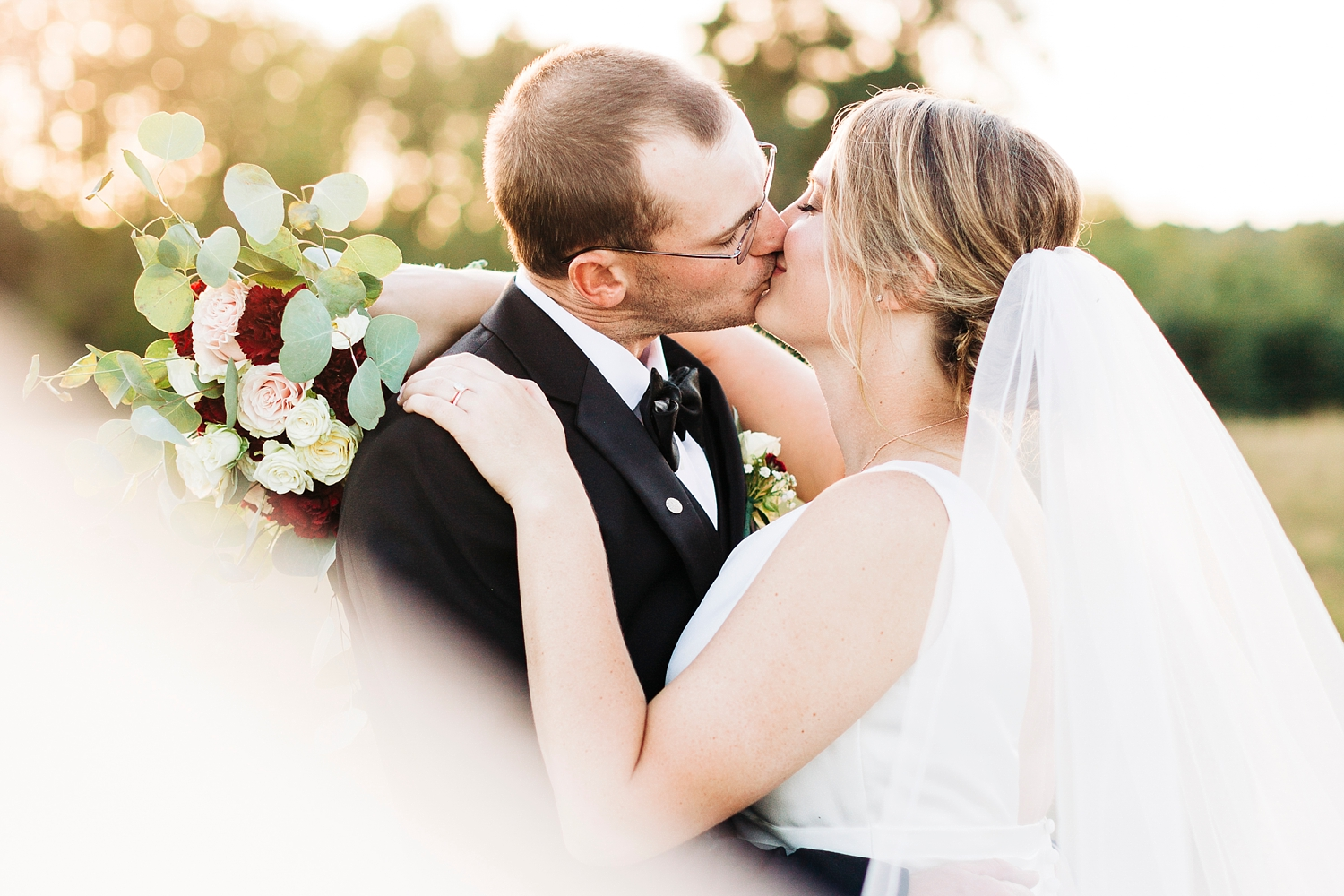bride and groom kiss outdoors