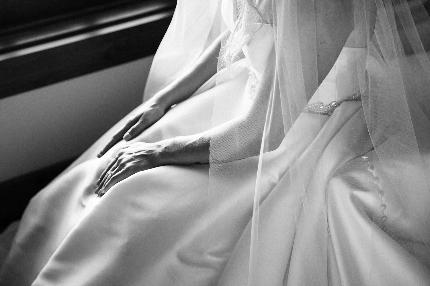 bride's hands rest in her lap on her wedding gown skirt