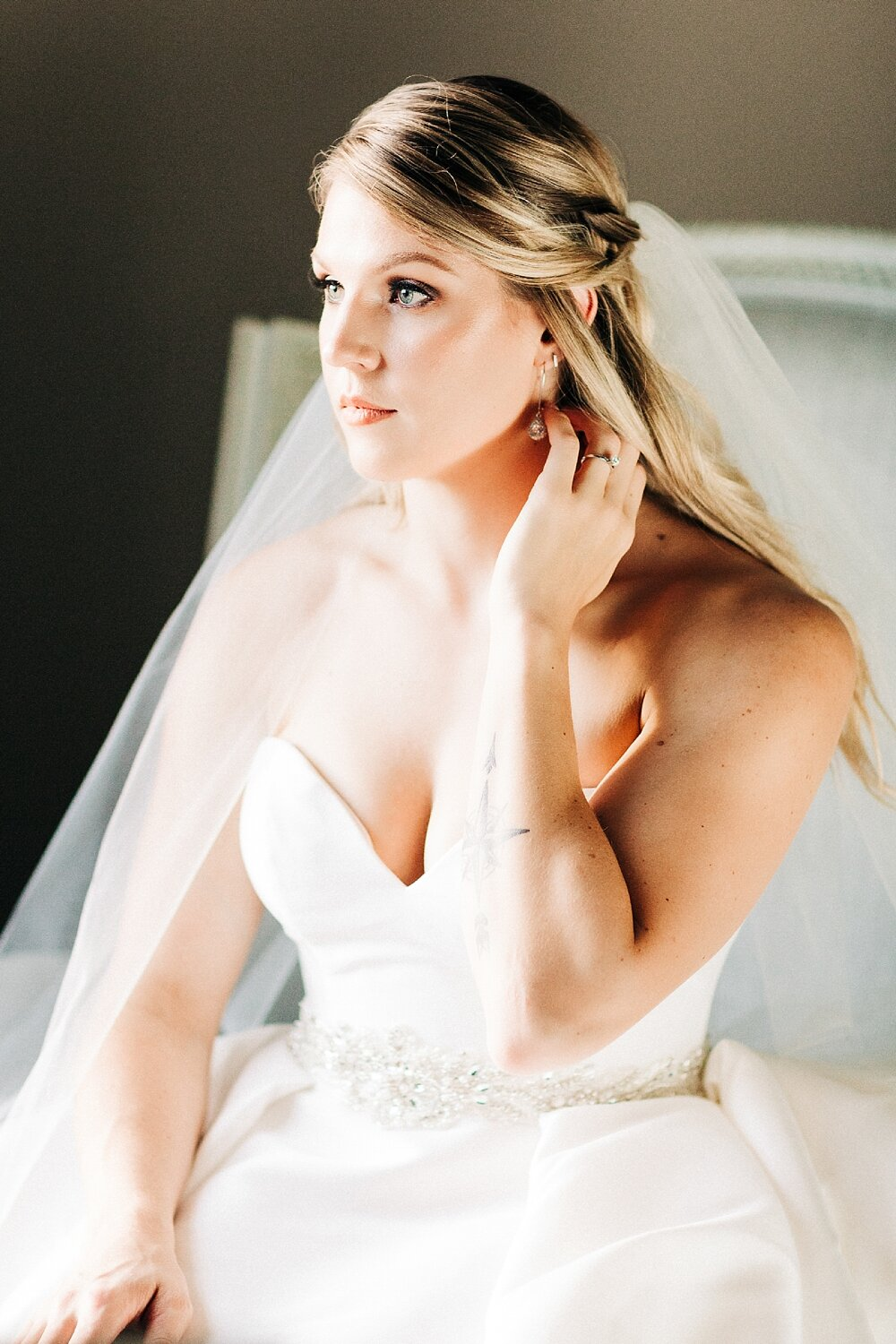 bride looks out a window while seated in a chair