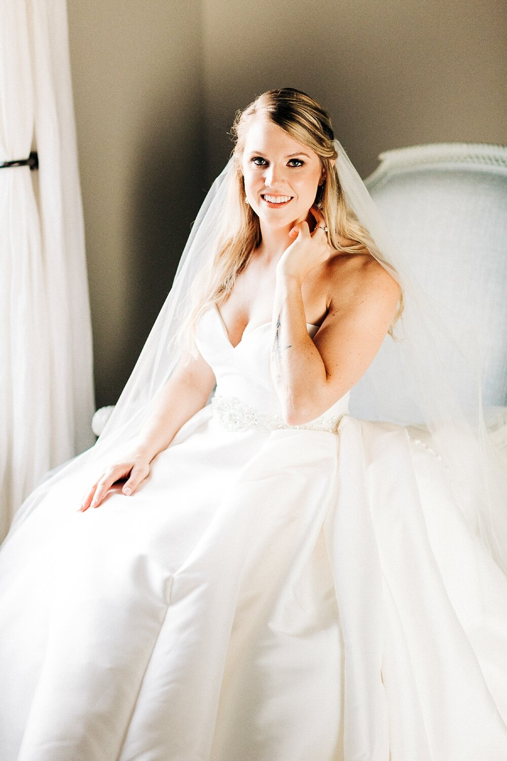 bride sits in an armchair and smiles