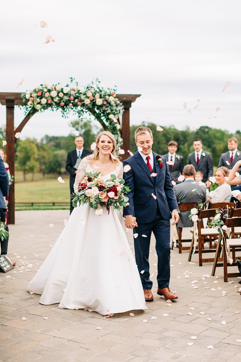 bride and groom exit their wedding ceremony with a rose petal toss
