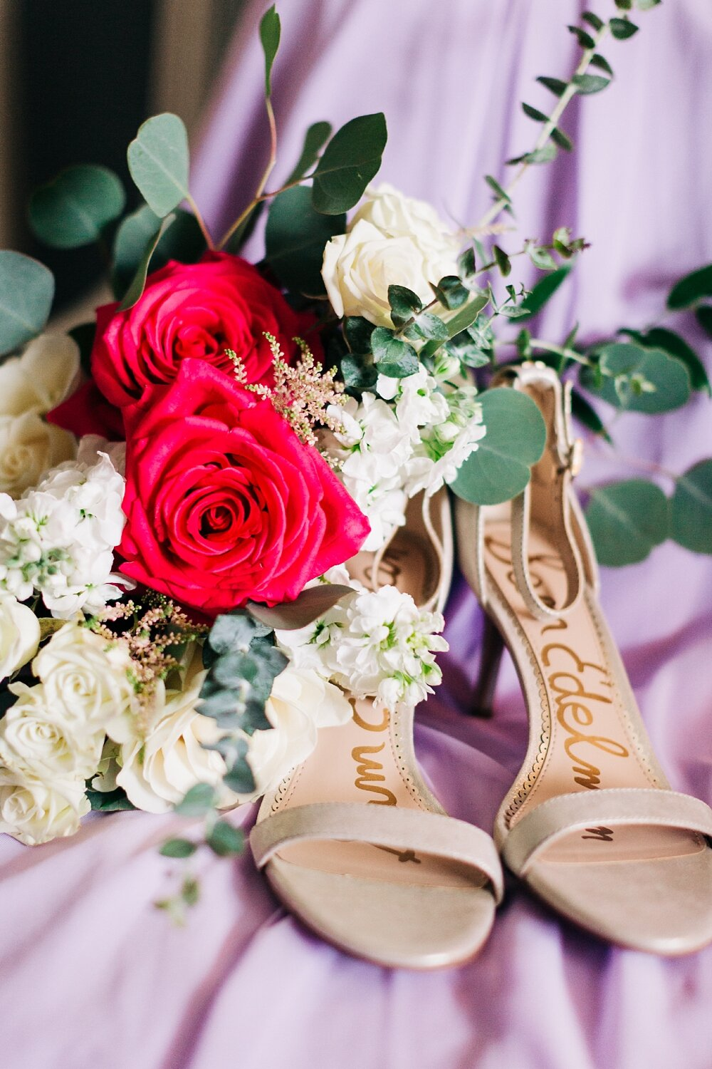 bride's shoes and bouquet on a purple bridesmaid dress