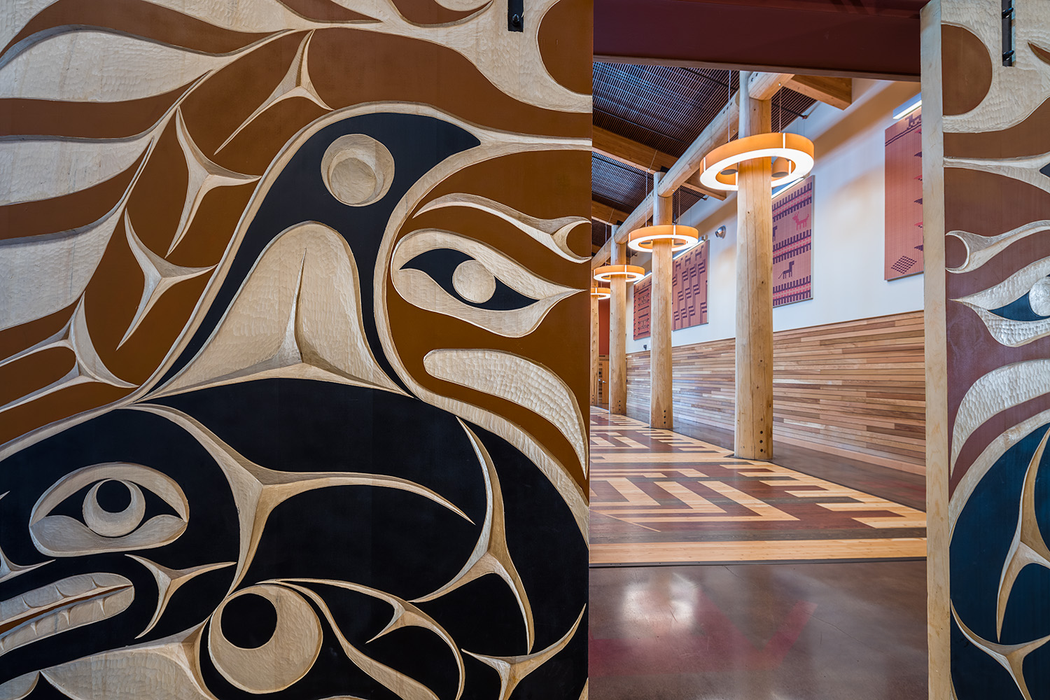 These beautiful carved doors feature traditional Coast Salish artwork. A view through to the Gathering Space provides a sense of depth and scale.
