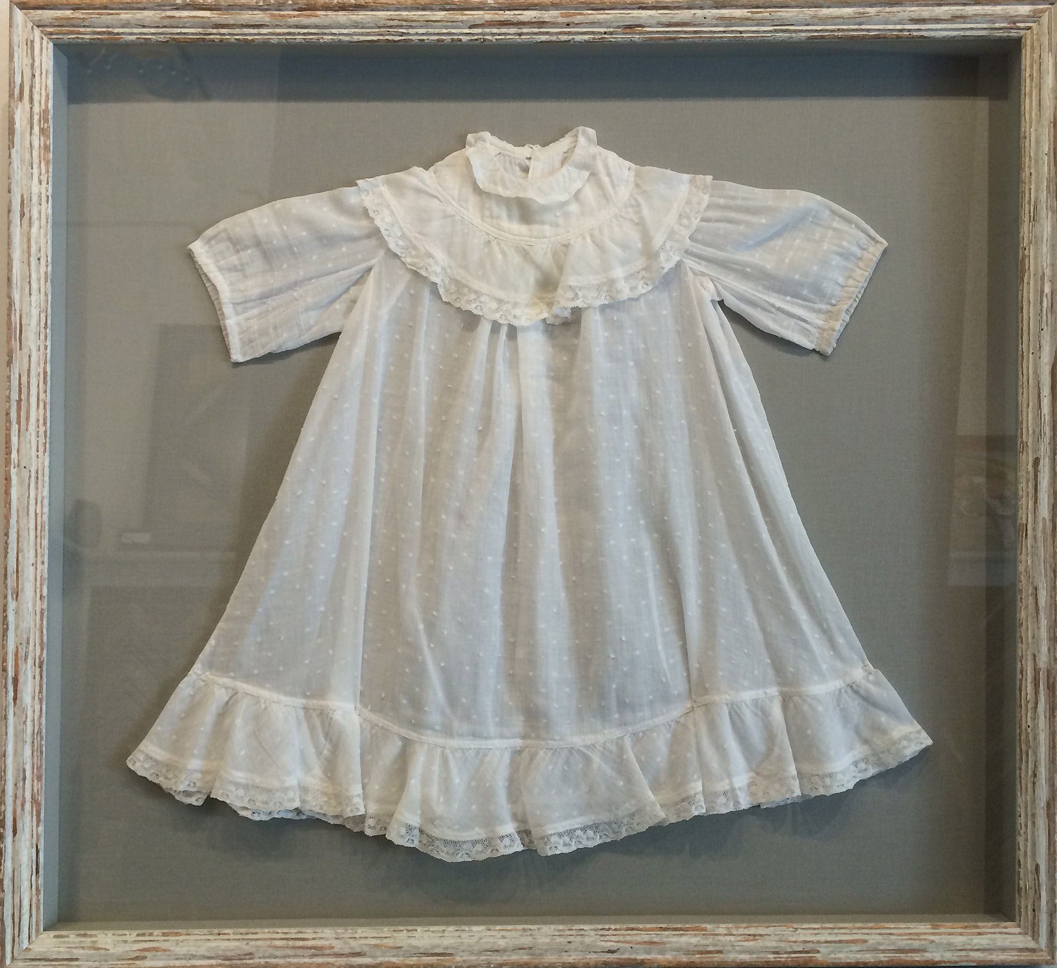 This child's Christening gown was floated on a neutral gray mat and placed into a vintage-looking white barnwood frame, .