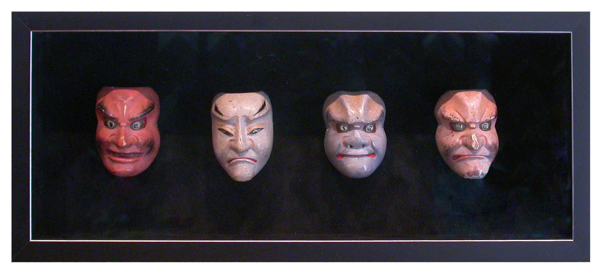 This collection of circa 1940's Japanese puppet heads seems to emerge from the darkness. The effect is created by the use of a black velvet lining within a black shadow box frame.