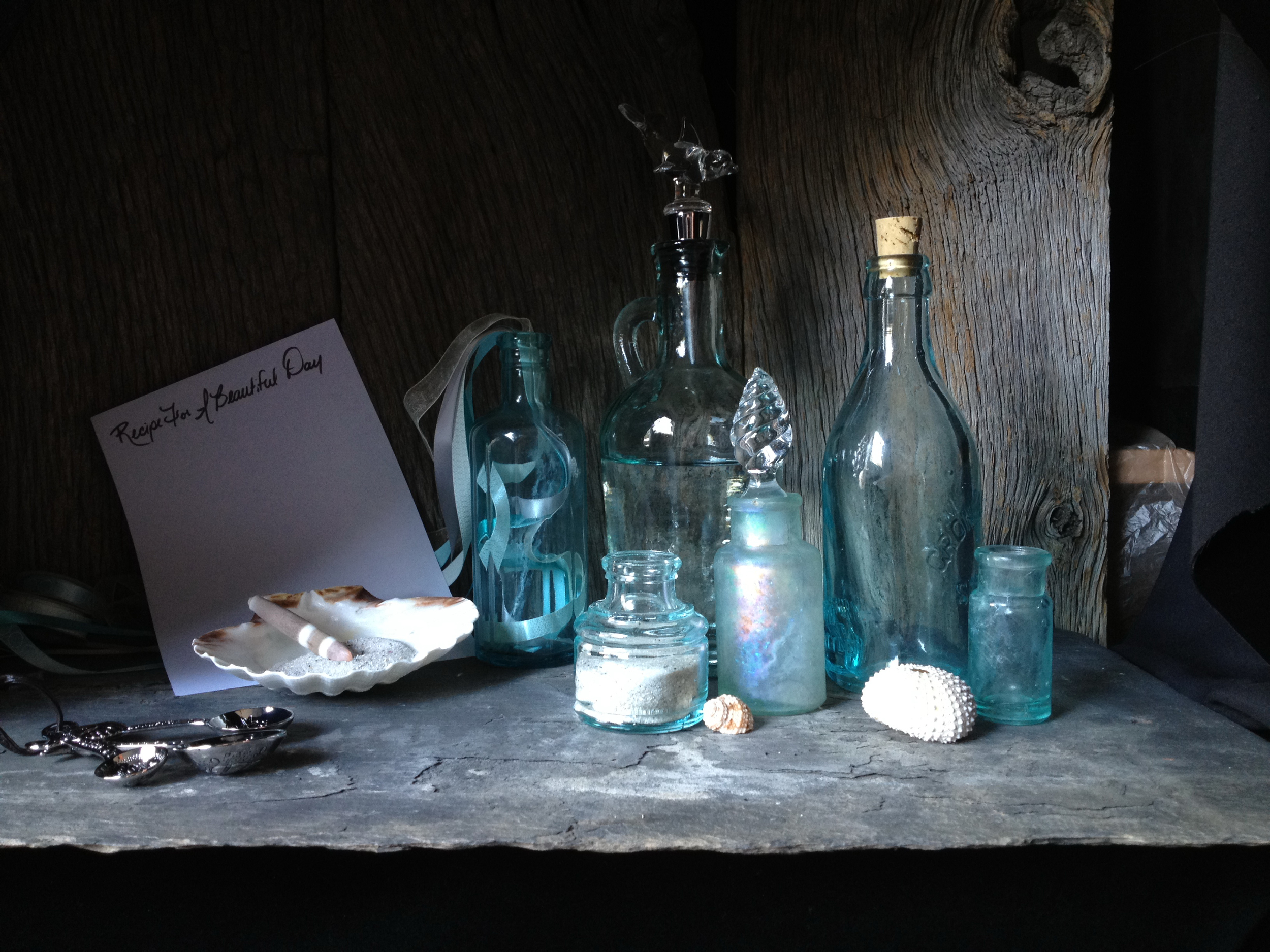 First, I placed weathered barn wood and a slate roof tile into my shadowbox for the background and stage for my still life. The colors of these two natural items harmonized well and I felt that also created a nice ambiance for the story. Next, I added all the bottles and seashells I thought that I would be using onto the stage and arranged them in a visually pleasing manner.