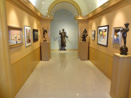 museum hallway with sculptures and paintings.