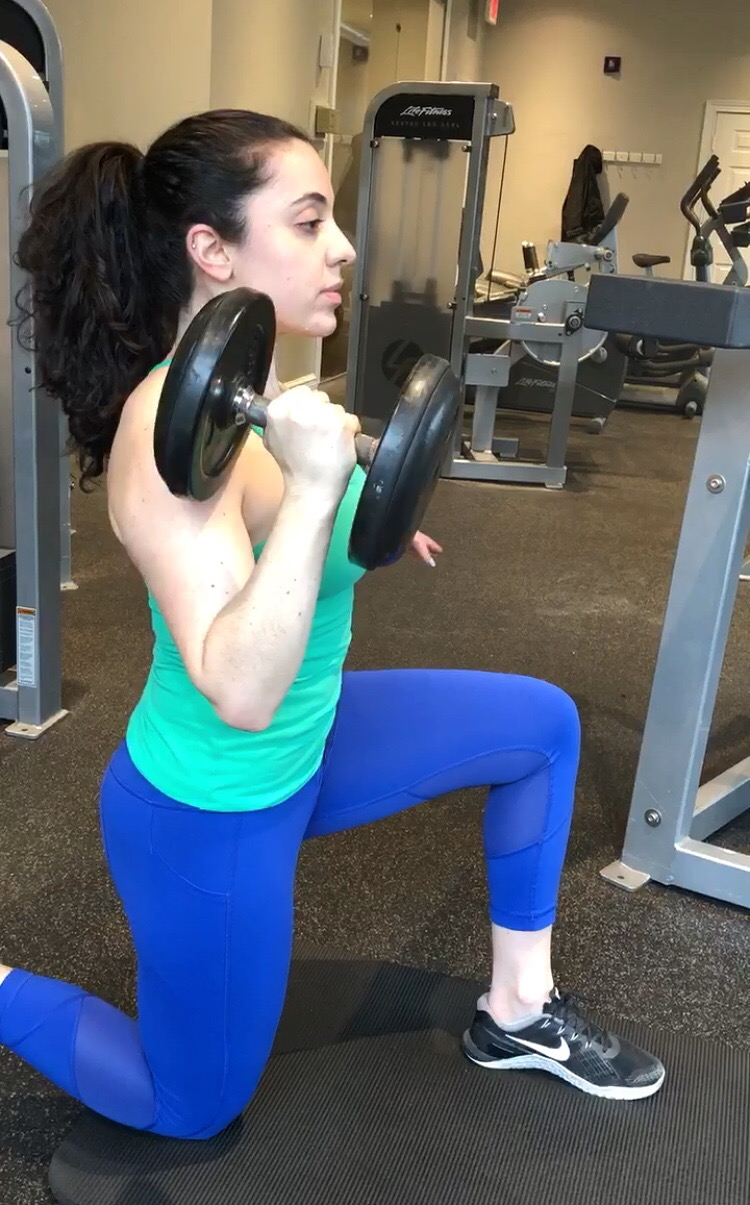 Doing shoulder presses in Nike Metcon cross-training shoes.