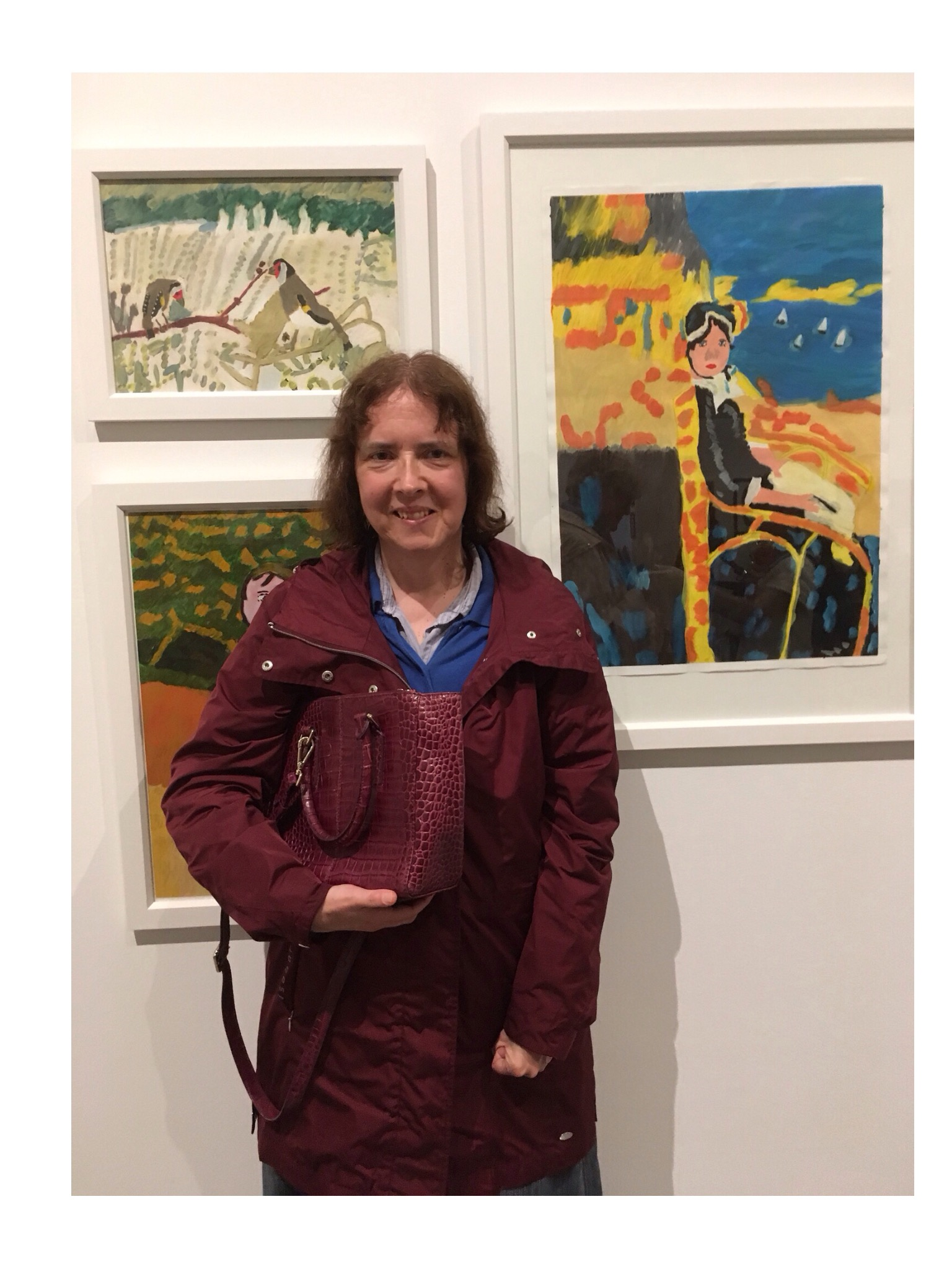 Madeleine Wilson in front of a few of her paintings on show.