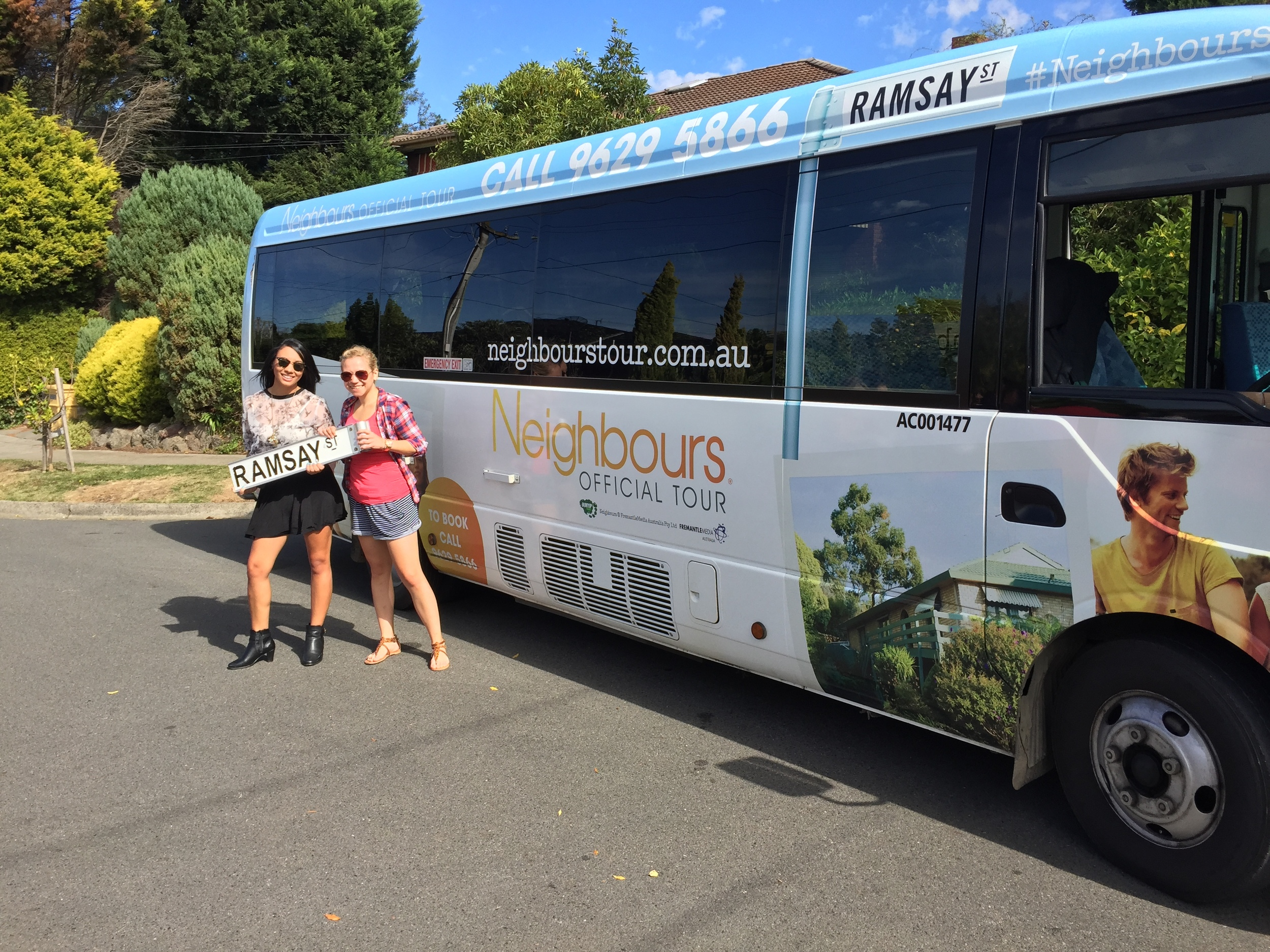 Fans holding Ramsay St sign in front of Bunyip Tours Bus