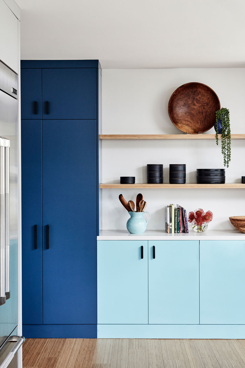 Taking away most of the upper cabinetry made a wall of built-in pantry closets a must for kitchen storage.