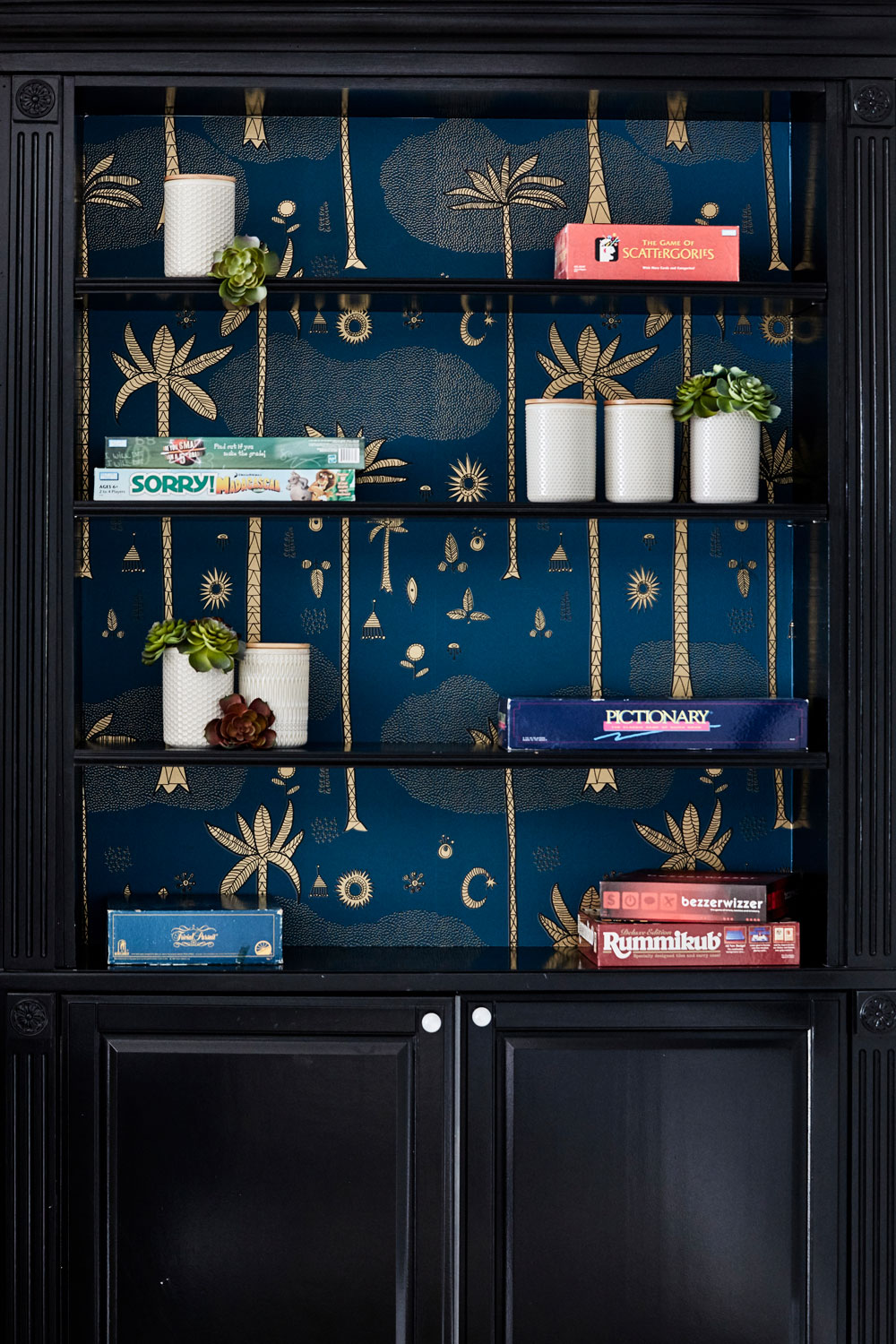 Justina Blakeney's Cosmic Desert wallpaper from Hygge & West is the coolest backdrop for these black built-in cabinets.