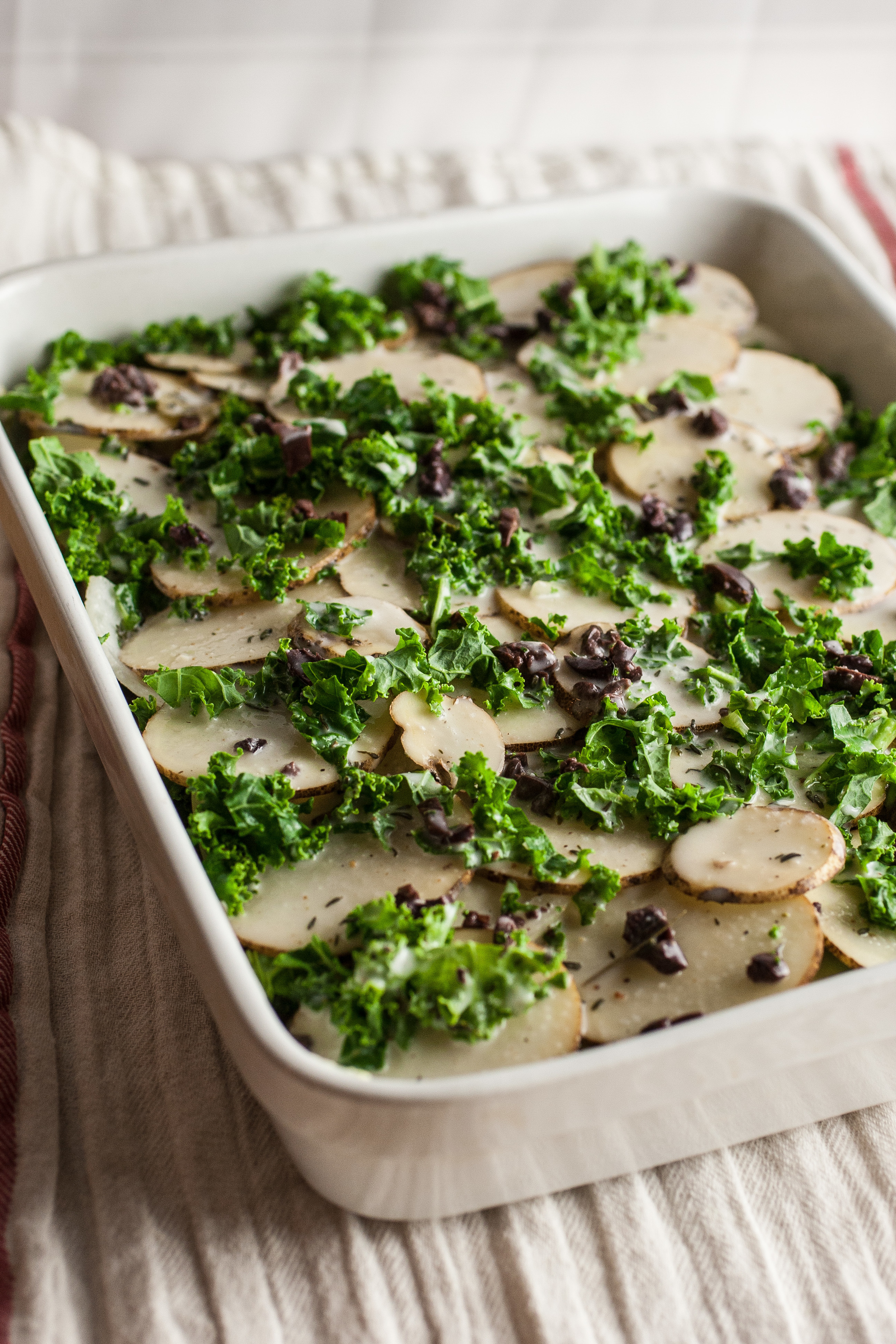Produce On Parade - Greek Scalloped Potatoes Gratin - Creamy and slightly sweet, this comforting herbed Greek Scalloped Potato Gratin is accompanied by green kale, salty Kalamata olives, and juicy yellow onion.
