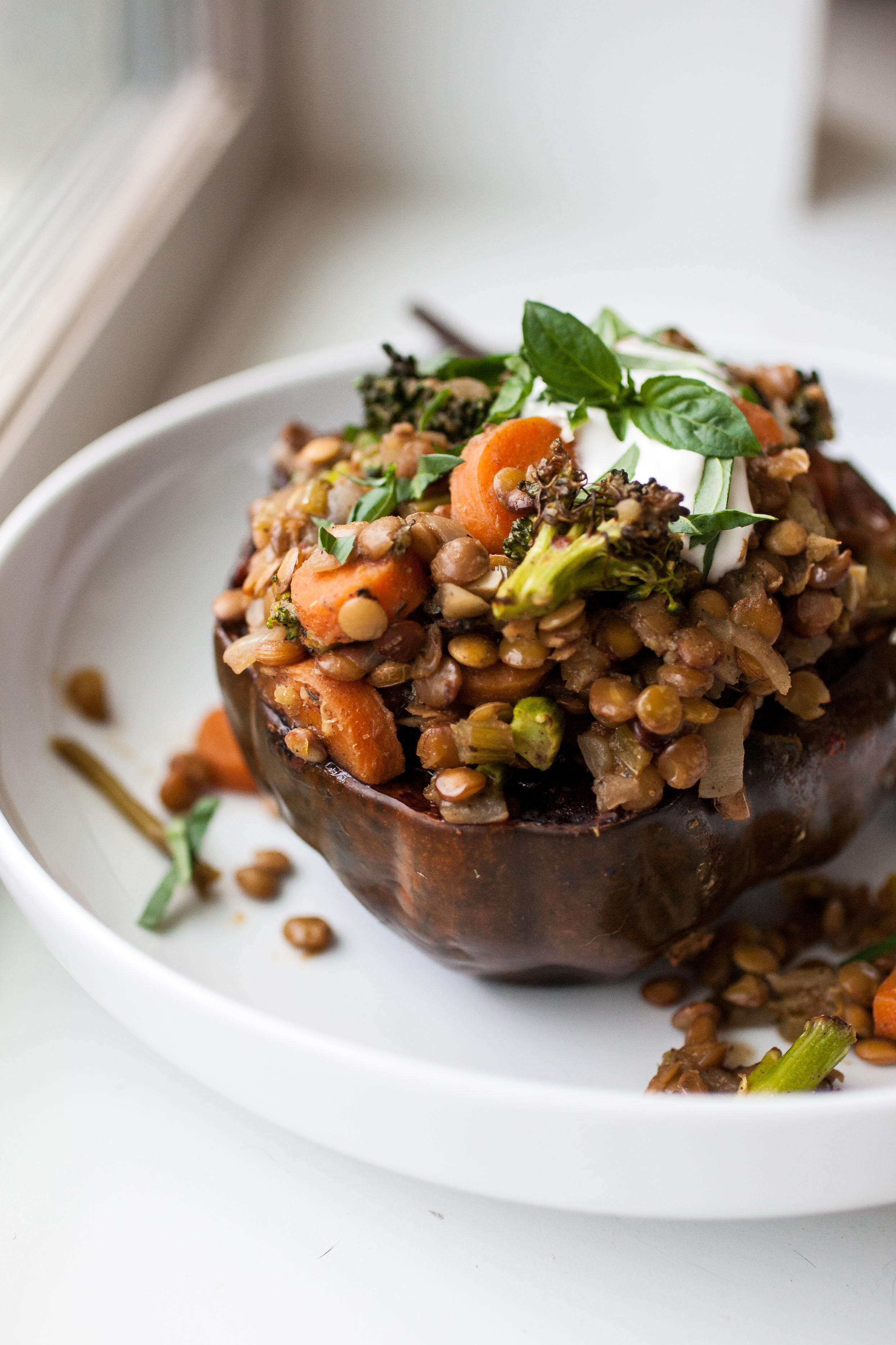 Produce On Parade - Garam Masala Lentil & Vegetable Squash Bowls  - Spiced garam masala lentils combine with an assortment of savory vegetables, nestled in a roasted acorn squash half all topped with vegan sour cream and fresh basil.