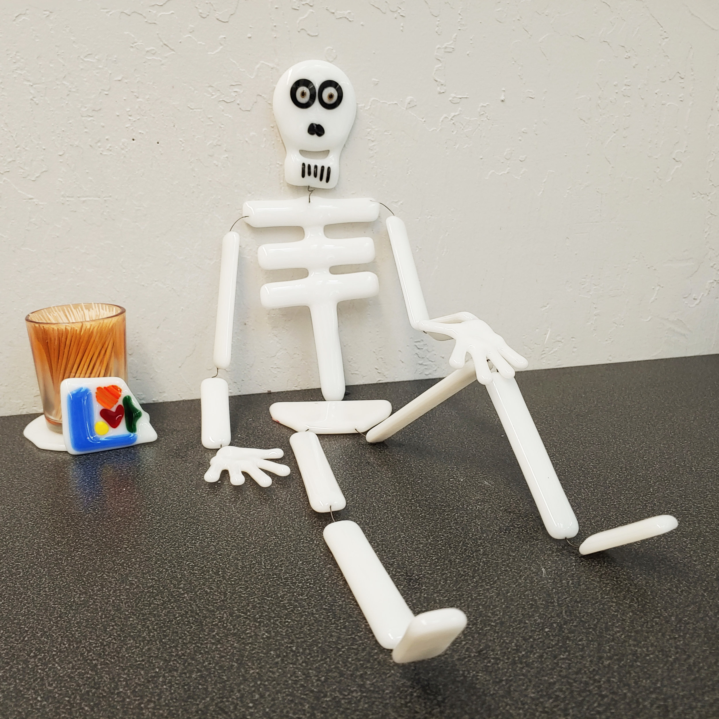 Skeleton - October 26, 5:00 PM - 6:30 PMThe perfect mix of spook and whimsy, these fun skeletons are a easy way to spook up your front door or any window. Using high temperature wire, we'll link together the bones for a funky fused friend. Skills: glass cutting, metal inclusions Ages: 12+