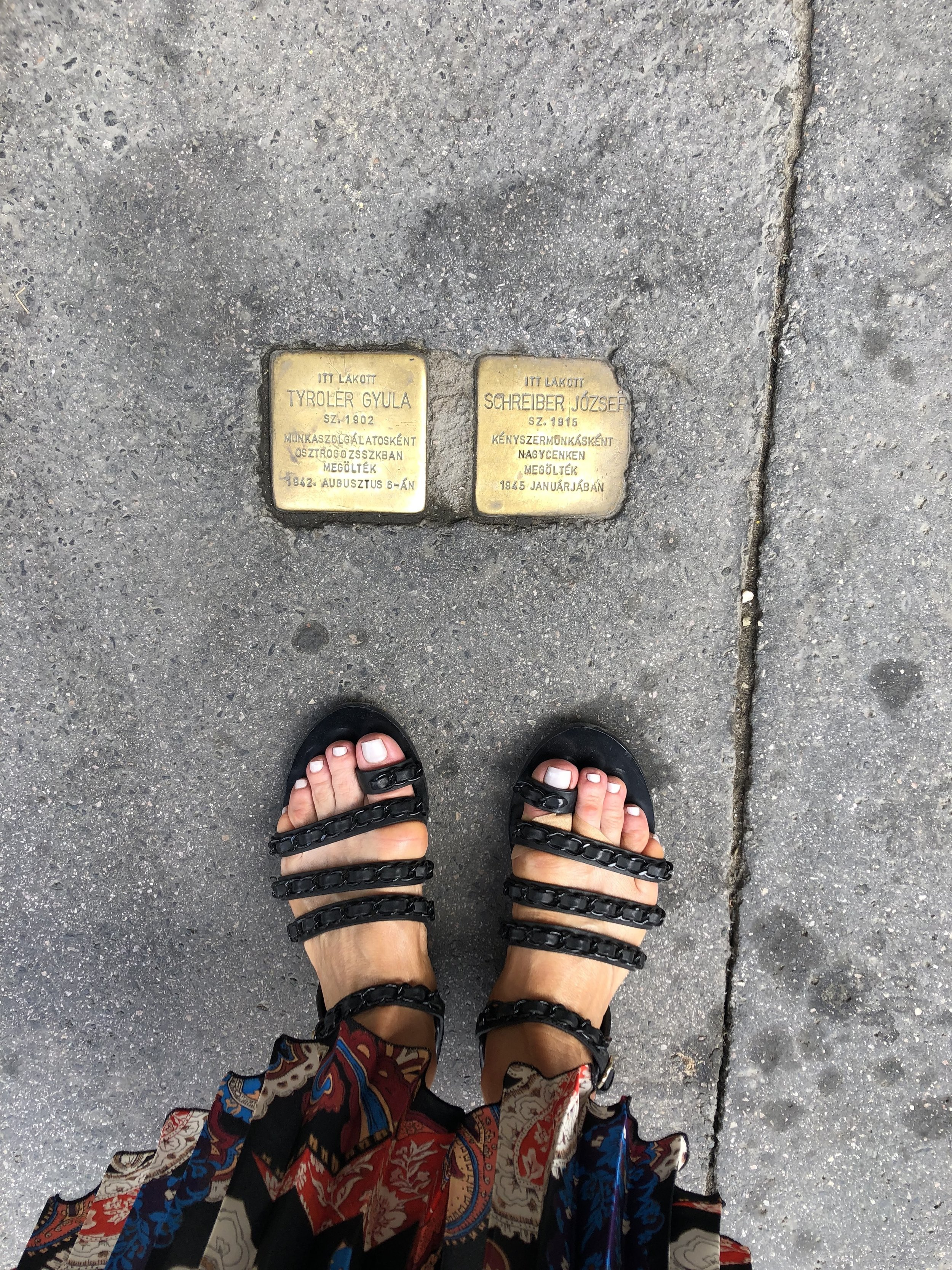 Standing in front of plaques marking the names of the families that lived there before being herded off to ghettos and death camps. These are the sobering reminders of the atrocities this community bore. Chanel chain sandals,    A World Curated pleated skirt.