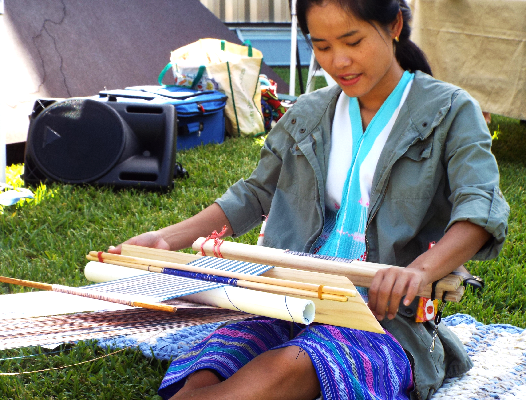Sa Nay Ma demonstrating the art of creating scarves with a back-strap weaving loom.