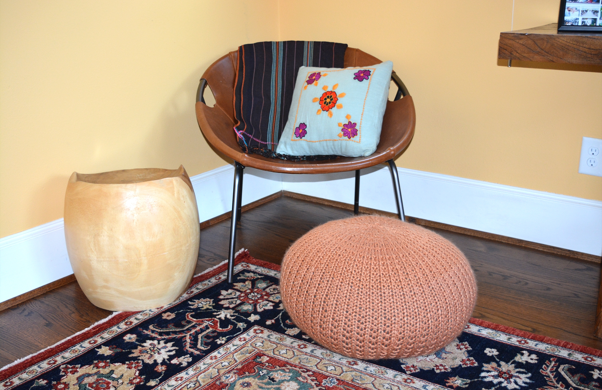 The brown floor pouf and embroidered blue pillow accent the rug and chair.