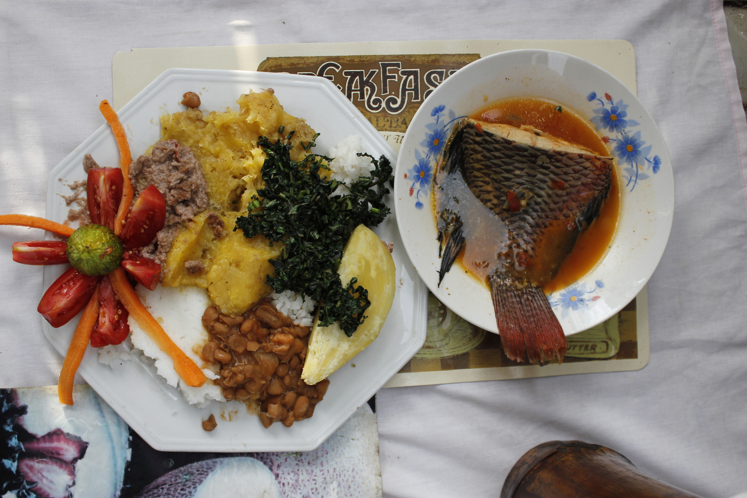 "the full combo: ""all foods""( posho, beans, matooke, rice, sweet potato) , greens, salad, g-nut and a delicious mputa (nile perch) tail.  ( photo : Moses Bwayo)"