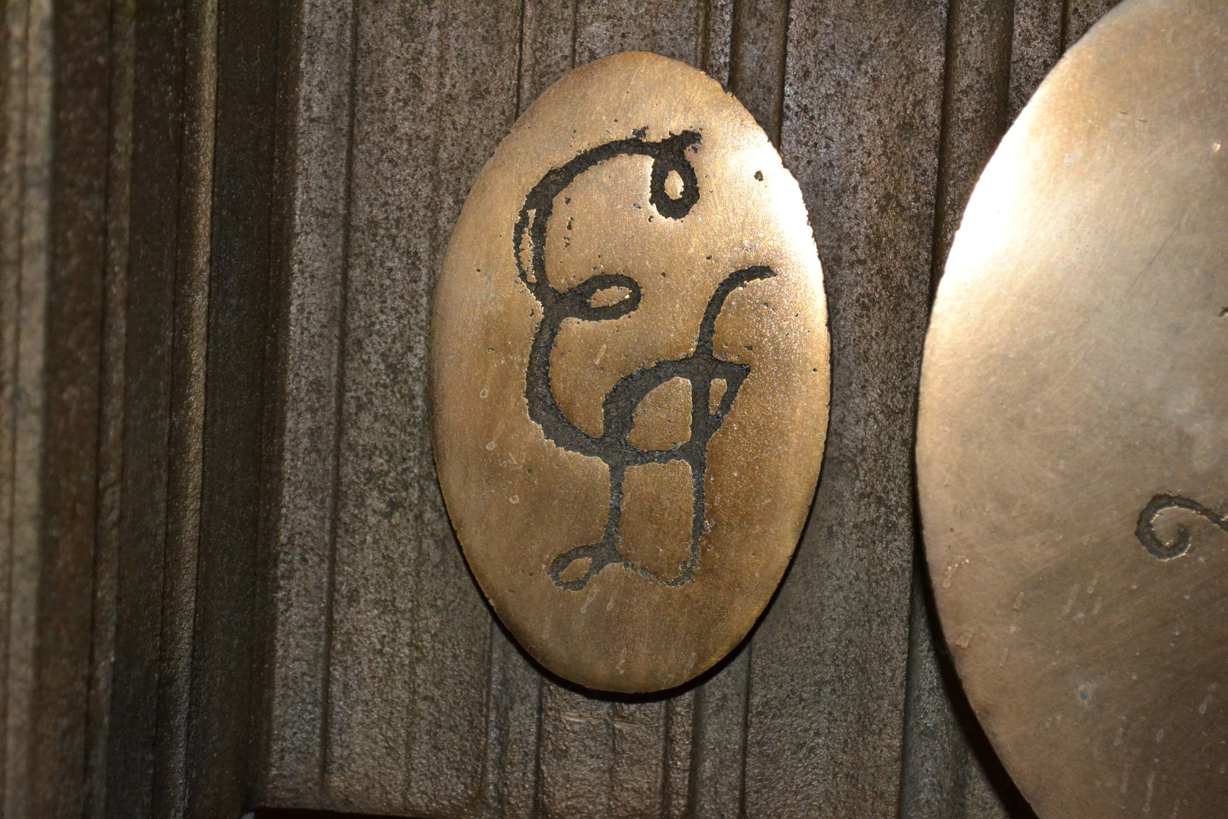 Emily Dickinson's highly stylized initials on a bronze medallion.