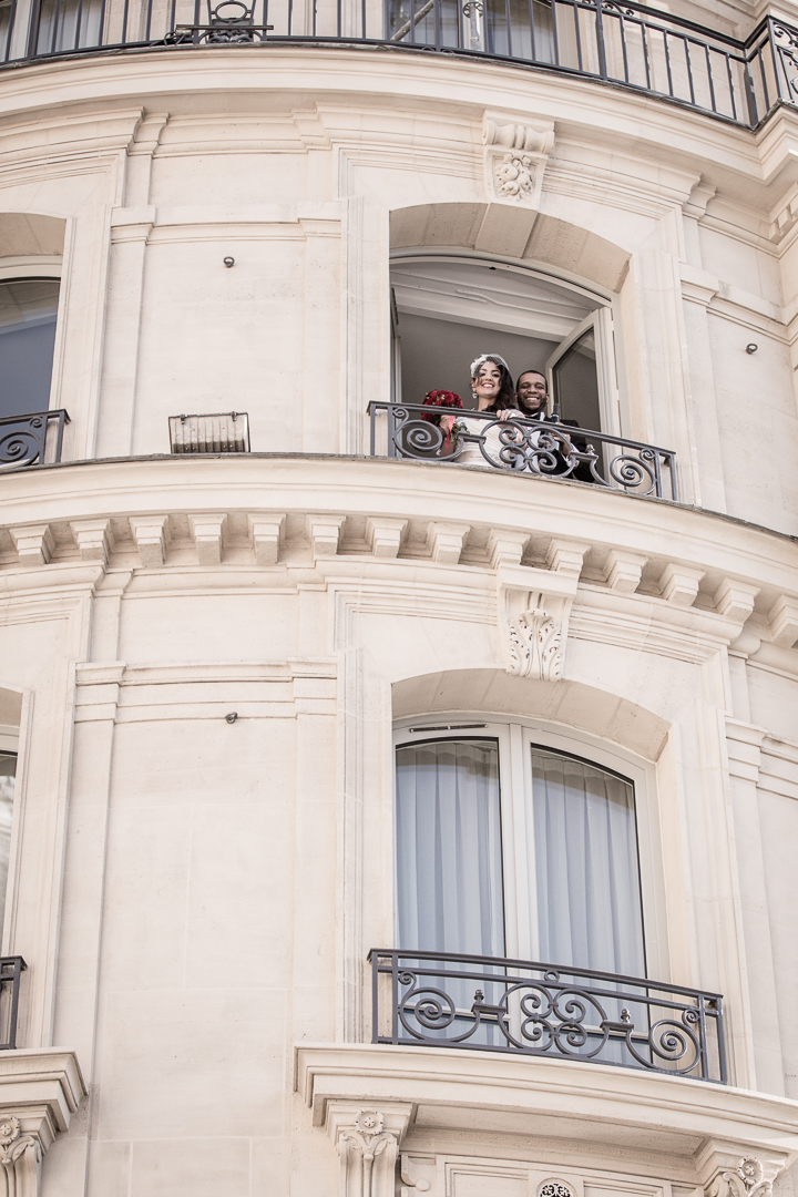 A bride and groom smile from their suite at the Hilton Opera Paris. Destination Wedding Photography - Amy Stallard Photography