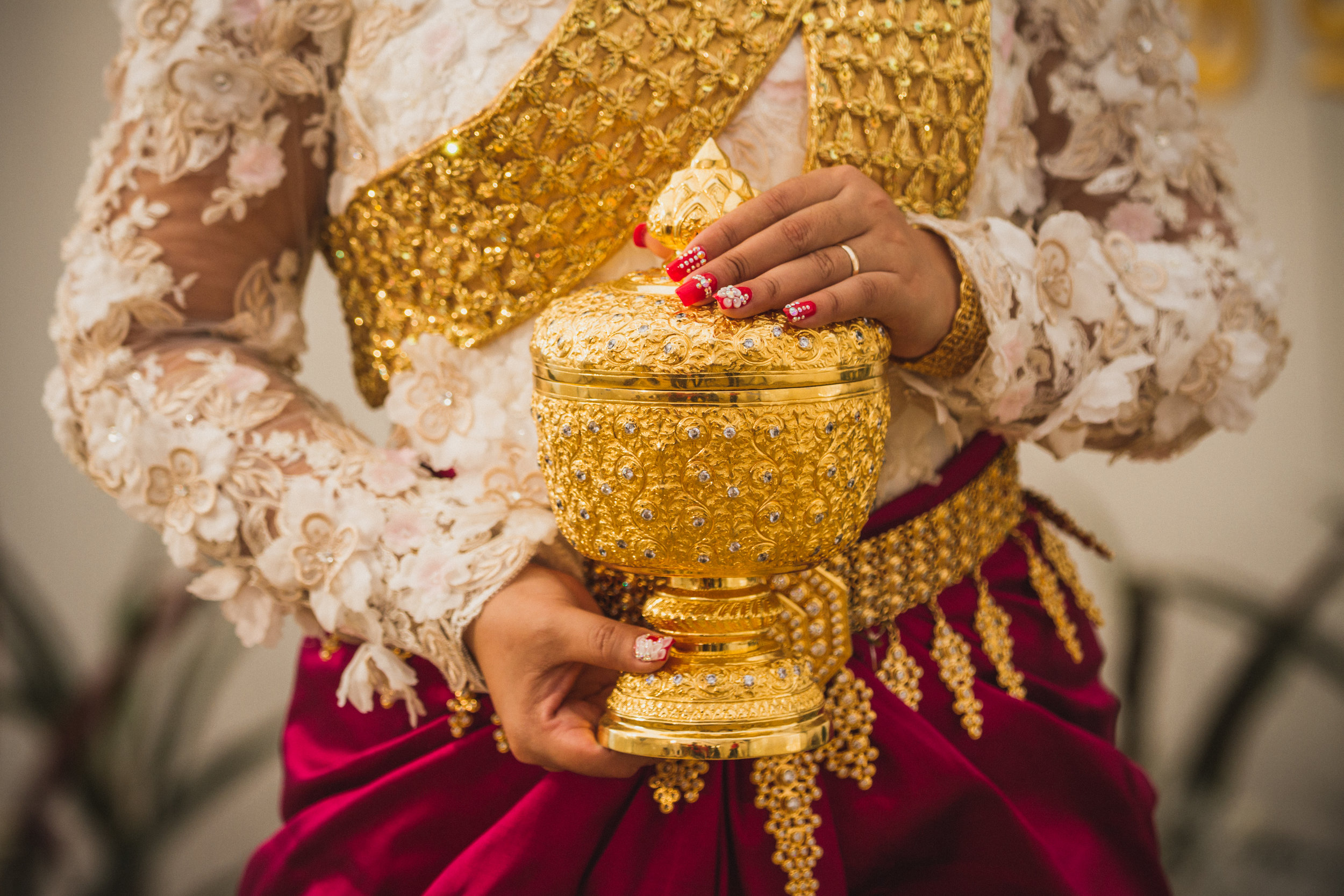 A bride holds a traditional Khmer vessel in Phnom Penh, Cambodia. Destination wedding photography (c) Amy Stallard