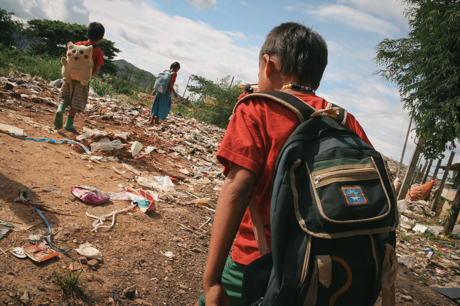 Schoolchildren walk through a garbage dump on their way home near Mae Sot, Tak Province, Thailand