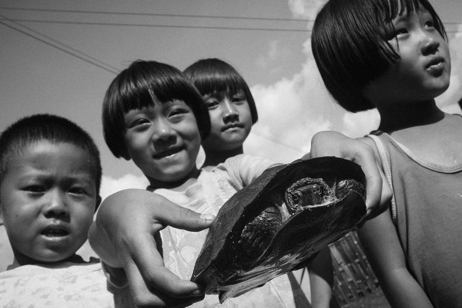 Kachin girls play with their pet turtle in Baan Mai Samakee, Chiang Rai, Thailand