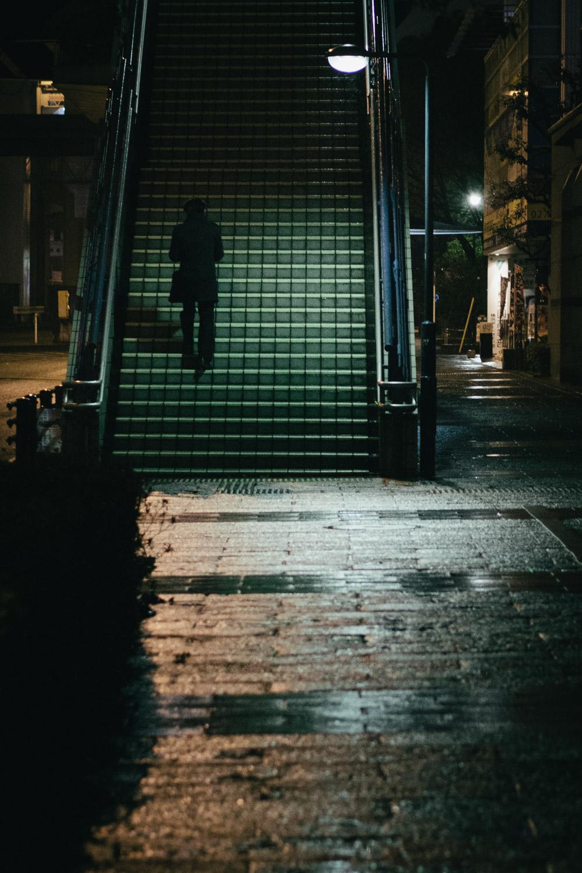 A salaryman walks up stairs on a rainy night in Yokohama, Japan