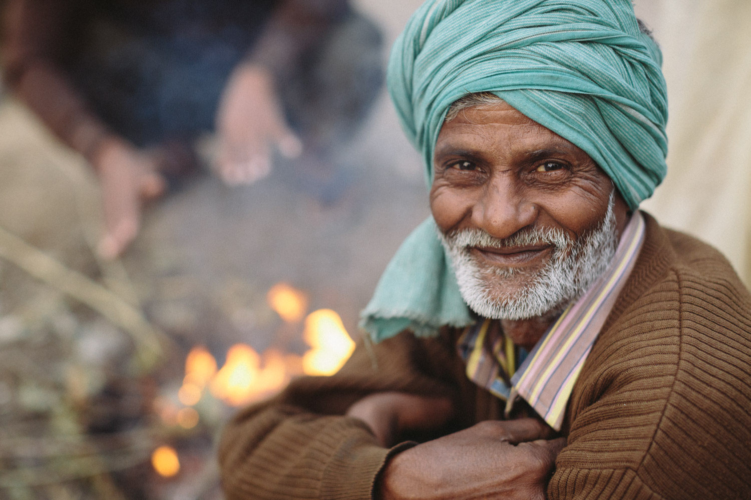 A man sits by a morning fire in Agra, Uttar Pradesh, India