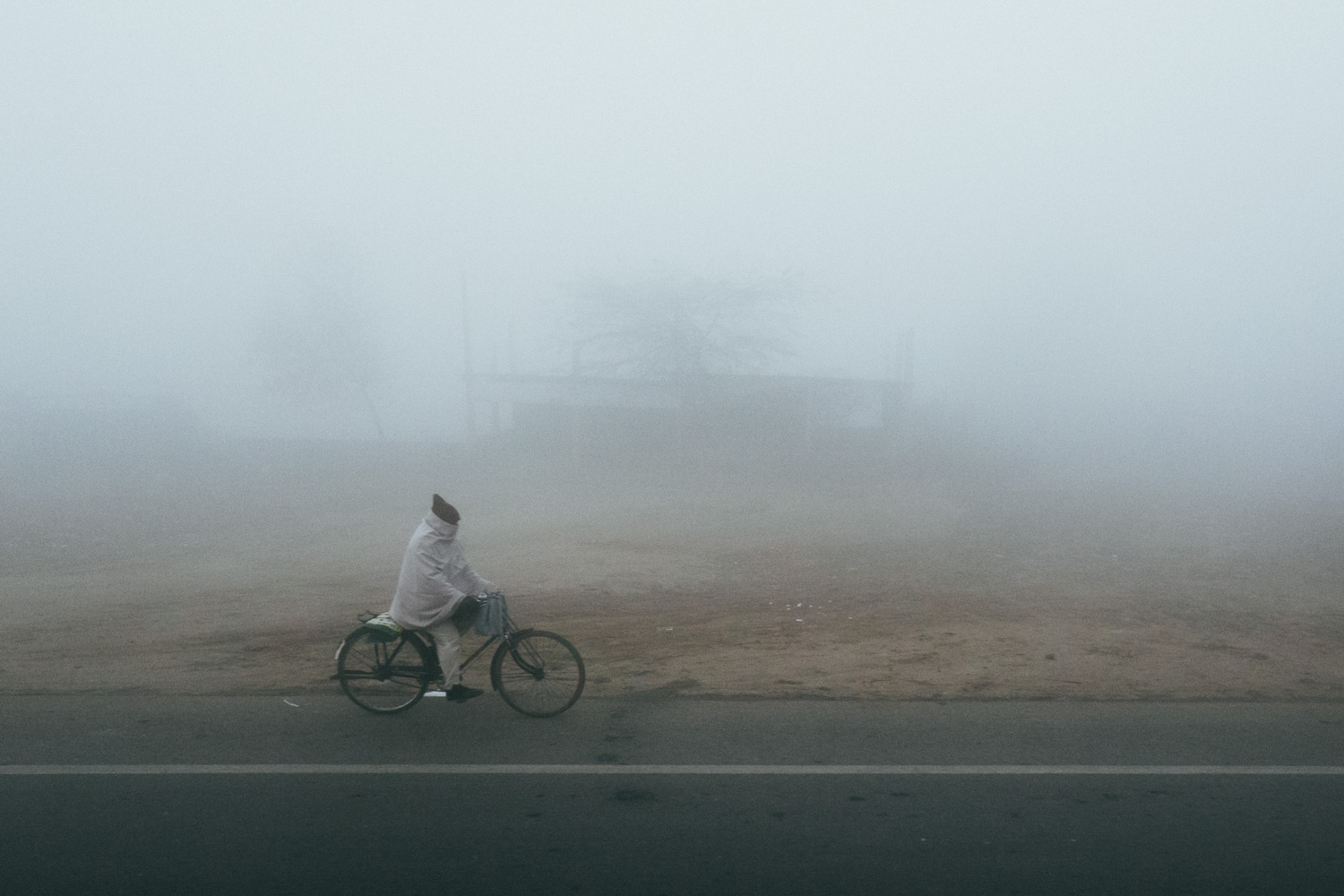A man rides a bicycle through morning fog along a highway near Delhi, India