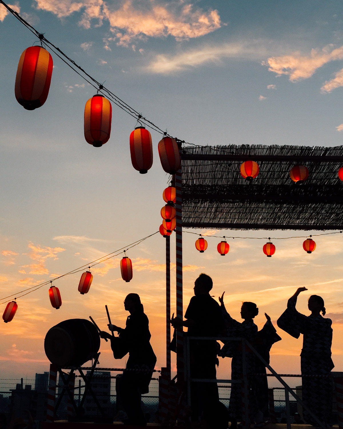 Silhouettes of dancers and drummers against the sunset at a Bon Odori dance festival in Kichijoji, Tokyo, Japan