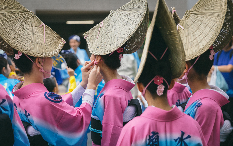Women dancers help each other prepare their costumes before the Koenji Awaodori dance festival in Tokyo, Japan