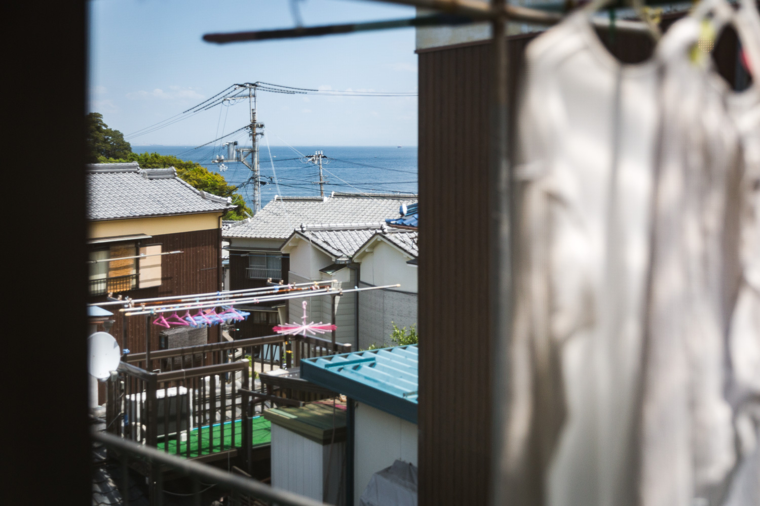 A view of rooftops, laundry, and the ocean from a house balcony on Awaji Island, Japan
