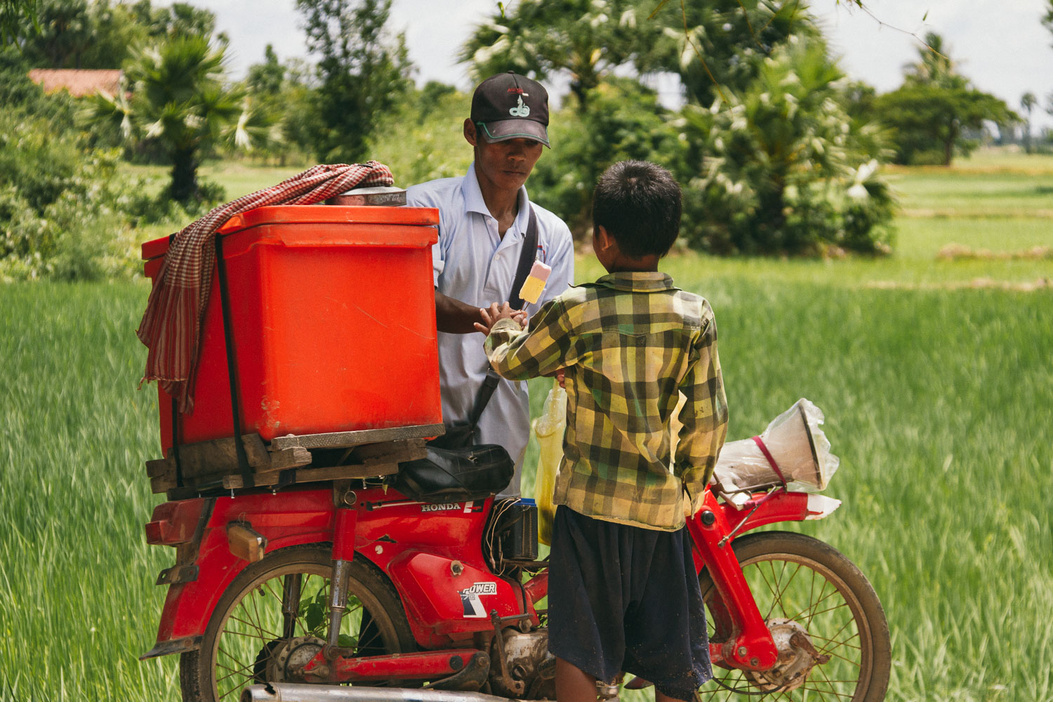 A boy buys ice cream from a motorbike vendor in Kampong Speu Province, Cambodia