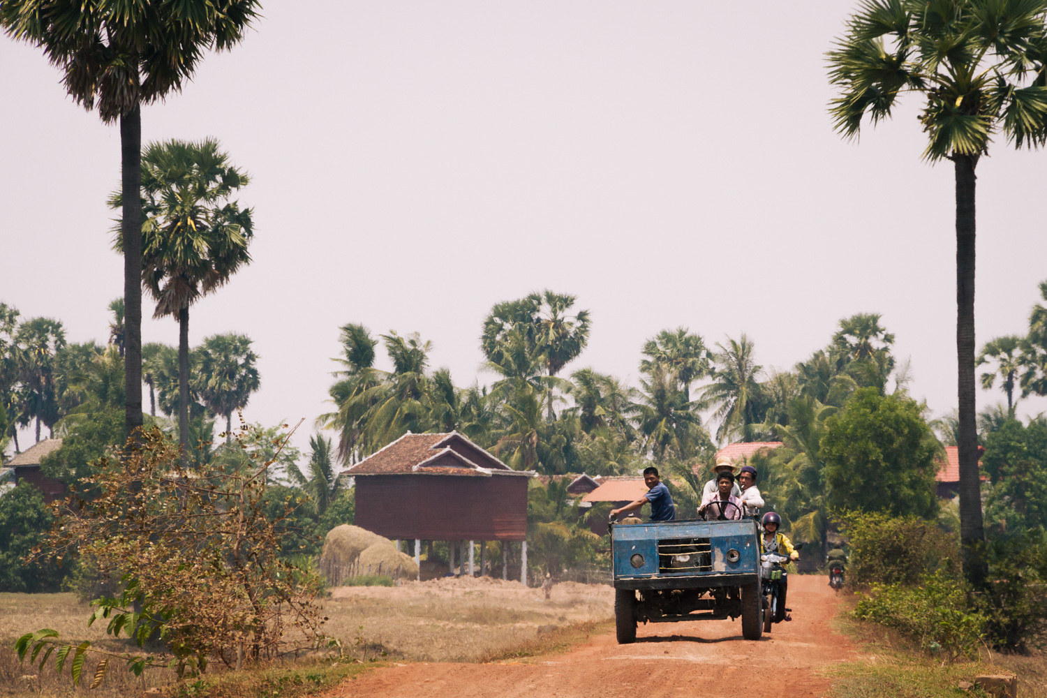 Farmers drive their truck on dirt road in Siem Reap Province, Cambodia