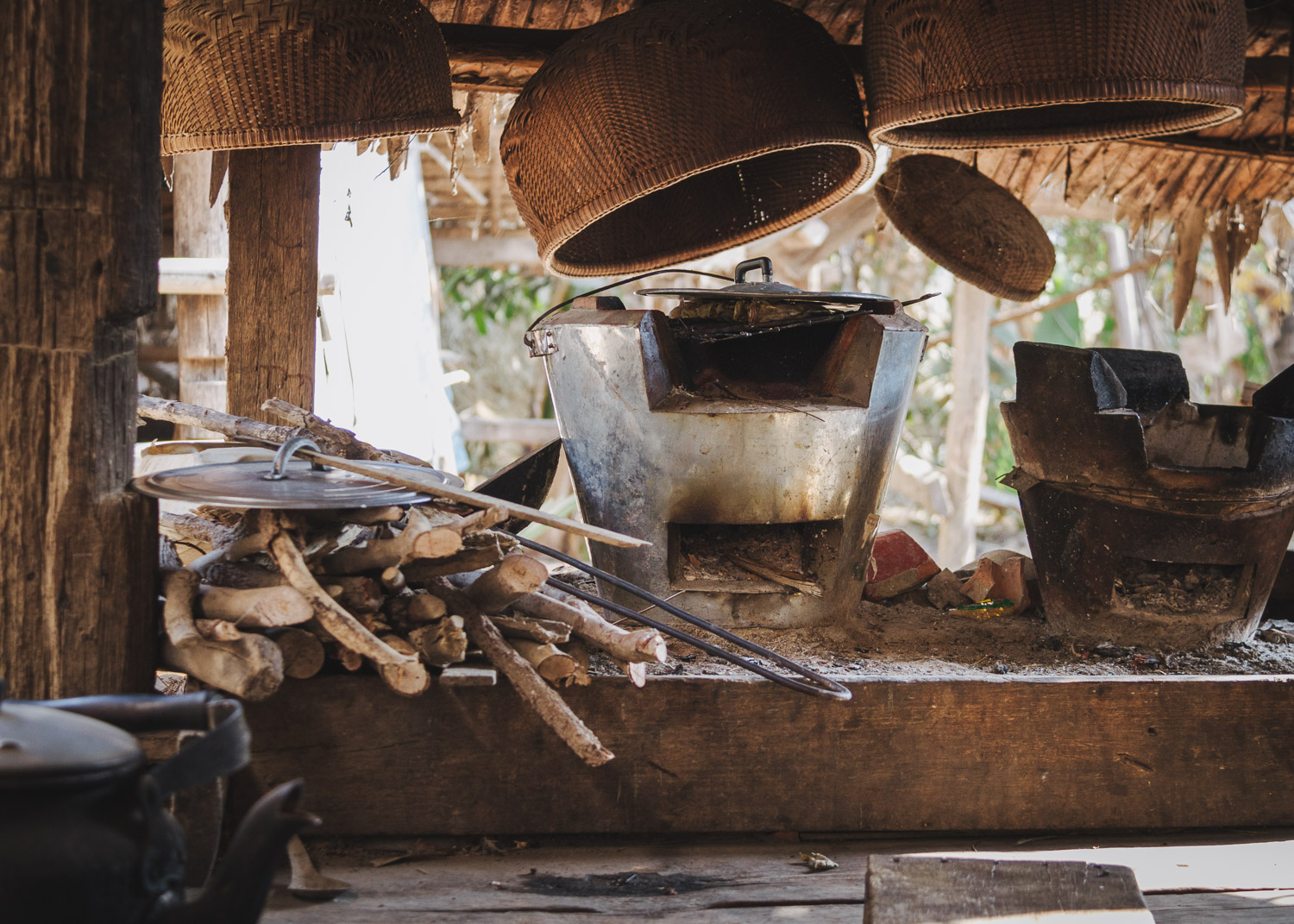 Wood-fired stoves, firwoood, and baskets in a rural kitchen in Siem Reap Province, Cambodia