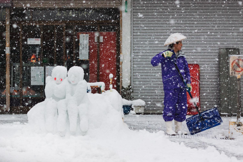 A man shovels next to snow figures in Nozawa Onsen, Nagano, Japan