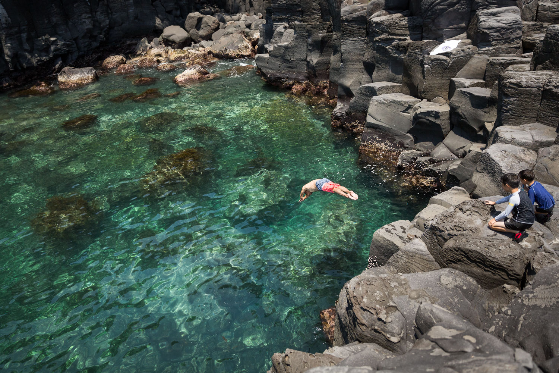 A man dives into clear emerald water along the Jogasaki Coast, Izu Peninsula, Japan