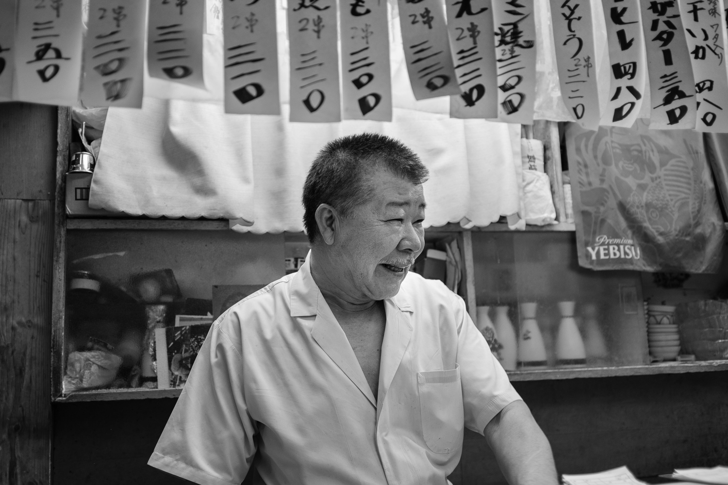 A yakitori chef smiles behind the counter of his restaurant in Shibuya, Tokyo, Japan