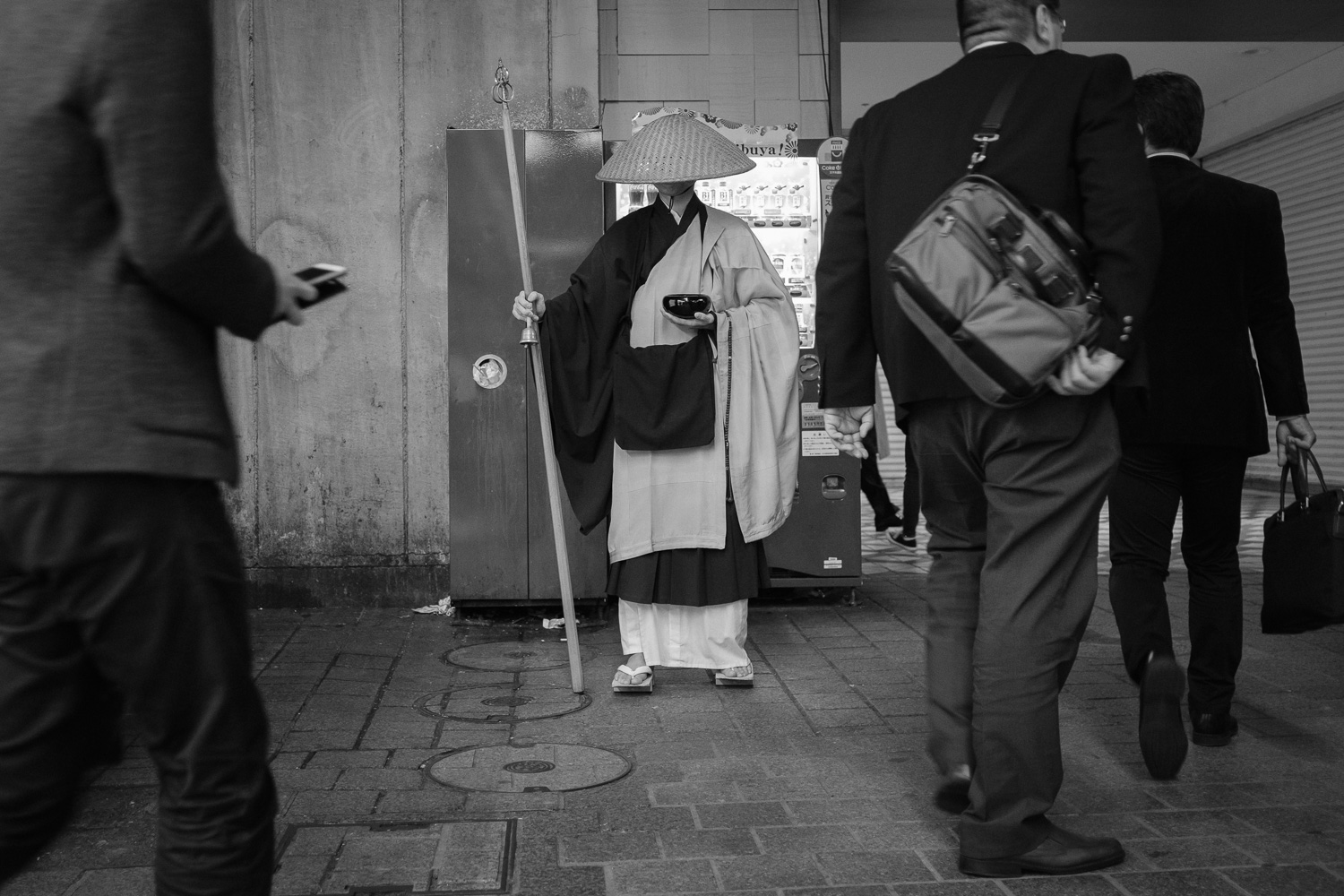 A Buddhist monk waits for alms during rush hour in Shibuya, Tokyo , Japan