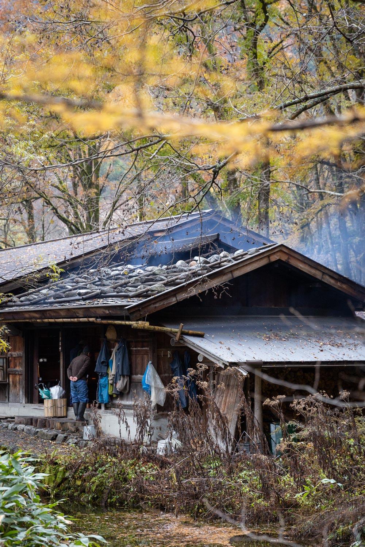 Irori smoke rises above a cabin during autumn in Kamikochi, Nagano, Japan