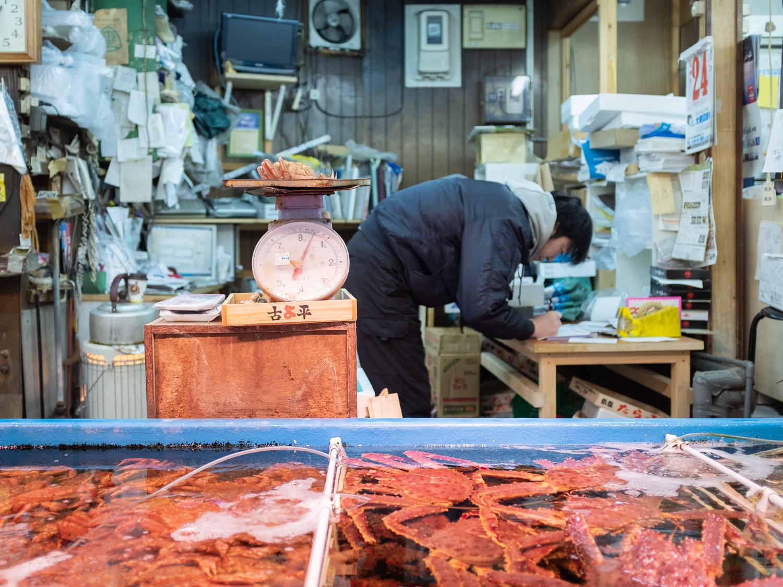 A man fills New Year crab orders at the Otaru fish market in Hokkaido, Japan