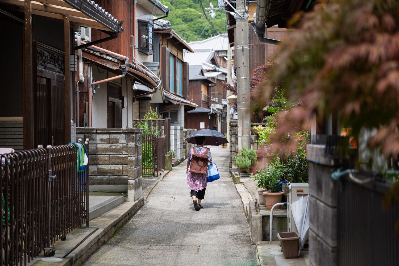 An old woman with a sun umbrella walks through a neighborhood on Awaji Island, Japan.