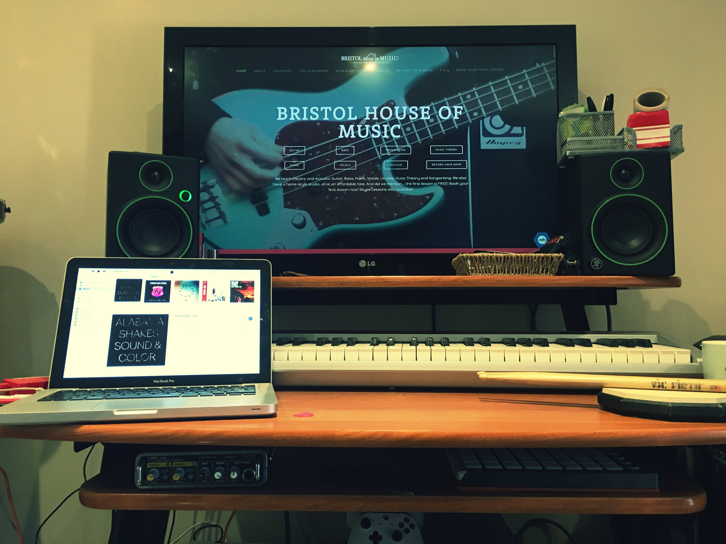 Macbook set up with monitor speakers, midi keyboard, audio interface, big screen, Logic Pro with recording capabilities good to go!