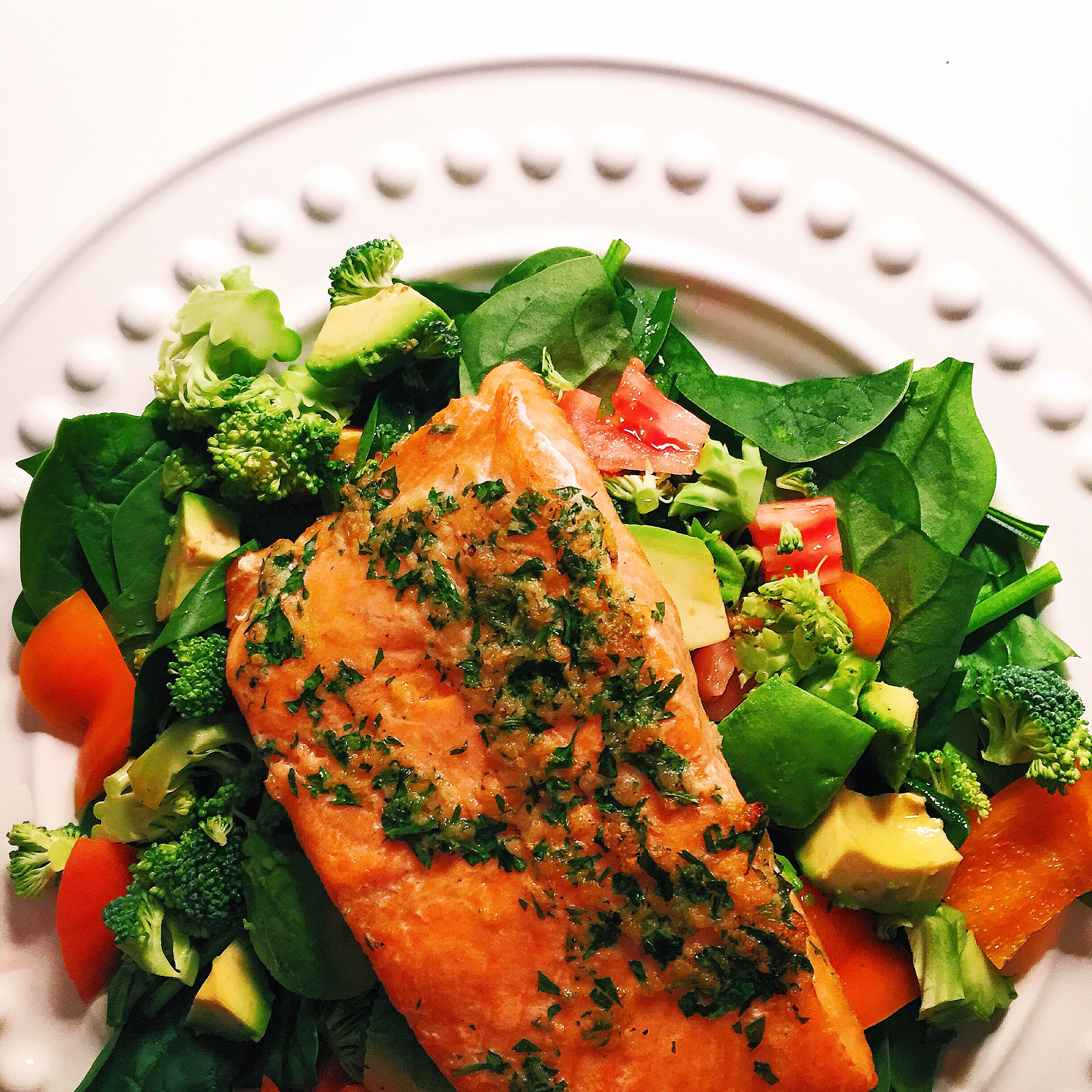 Broiled salmon over spinach salad