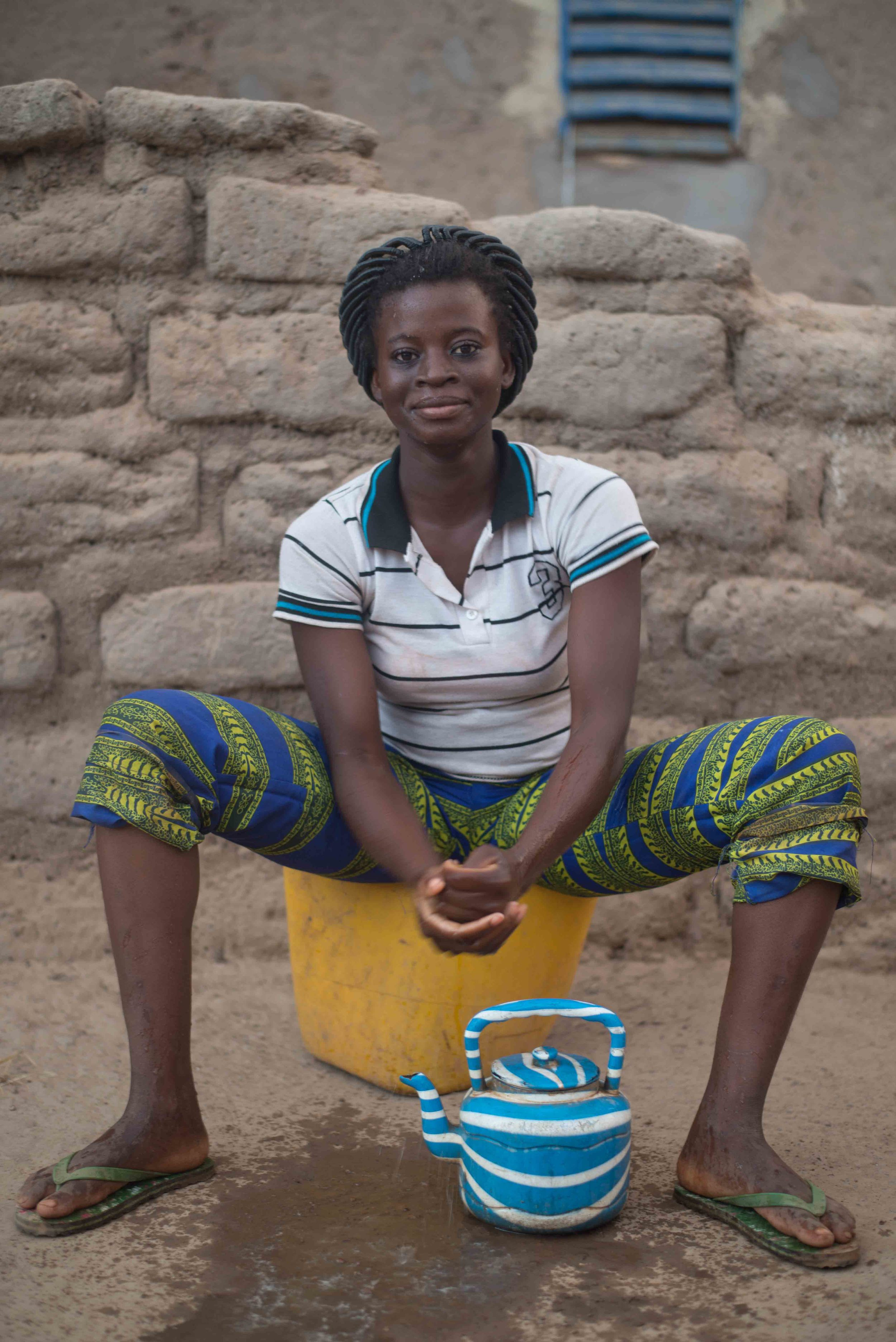 Zalisa demonstrates abulations with with a plastic teapot used for washing all over Burkina.