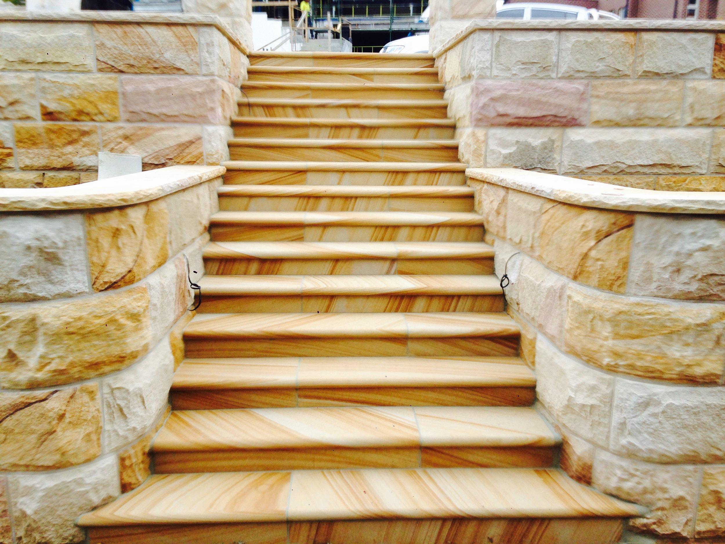 Elite Stonemasons- Kellyville project- medium brown bullnosed steps with brown range curved rockfaced walling (2).JPG